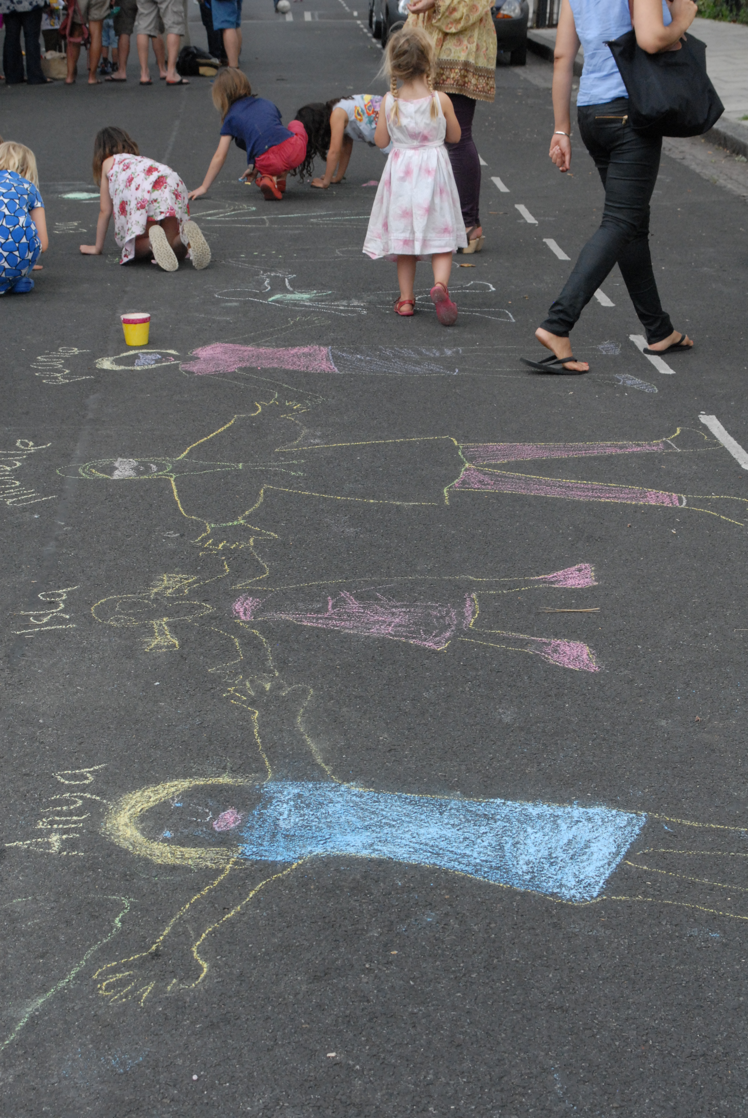Children drawing chalk people along the road during a Play Street session in Hackney