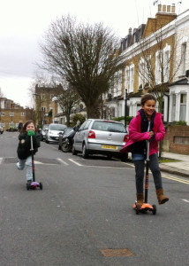 Two girls race down a street on scooters
