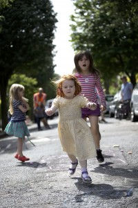 A 3 year old girl and her older sister hopscotch in the street