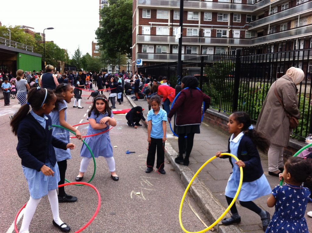A group of girls hula hoop in a busy Hackney play street