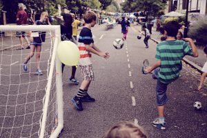Group of children play football in the street