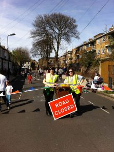 Two women wearing high-vis vests stand behind a Road Closed sign, at a play street session