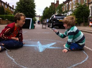 Two boys aged around 6 chalk draw in the street