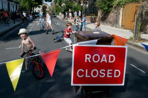 Children ride bikes, scoot and rollerblade in the street behind a Road Closed barrier